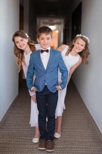 Junge in Kommunionsanzug mit zwei Mädchen in Kommunionskleid von Itsmydress